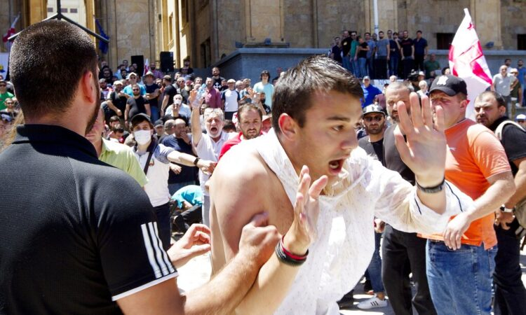 Opponents of the march push a man as they block off the capital's main avenue to an LGBT march in Tbilisi, Georgia, Monday, July 5, 2021. (AP Photo/Shakh Aivazov)