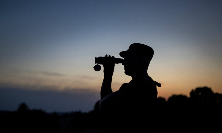 A member of the Lithuania State Border Guard Service looks through binoculars as he patrols on the border with Belarus, near the village of Purvenai, Lithuania. (AP Photo/Mindaugas Kulbis, File)