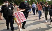 """Russian police detain an opposition activist with a poster reading """"Freedom to Alexei Navalny"""". (AP Photo/Alexander Zemlianichenko)"""