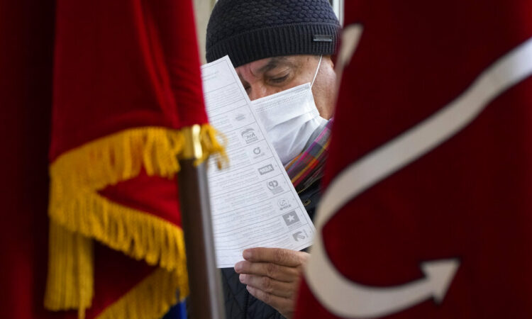 A man examines his ballot during the State Duma elections at a polling station in St. Petersburg, Russia. (AP Photo/Dmitri Lovetsky)