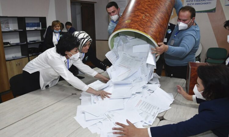 Members of an election commission remove ballots from a box to count them at a polling station after the presidential election in Tashkent, Uzbekistan, Sunday, Oct. 24, 2021. (AP Photo)