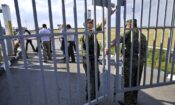 Members of OSCE (Organization for Security and Cooperation in Europe) mission walk behind a gate while visiting the Gukovo border checkpoint at Russia-Ukraine border in a small town of Gukovo. (AP Photo/Sergei Pivovarov)