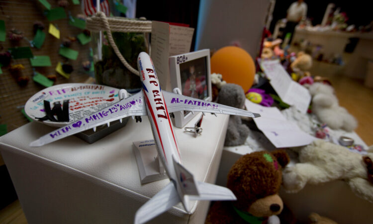 """A Malaysia Airlines miniature plane with a text reading """"RIP MH17"""" is displayed at a memorial site for the victims of the MH17 air disaster at Schiphol Airport in Amsterdam, Netherlands (AP Photo/Peter Dejong)"""