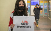 """A woman holds a poster reads """"I'm/we're Raman Pratasevich"""" as she waits to see passengers of the plane, carrying opposition figure Raman Pratasevich which was traveling from Athens to Vilnius and was diverted to Minsk after a bomb threat, after its landing at the International Airport outside Vilnius, Lithuania, Sunday, May 23, 2021. (AP Photo/Mindaugas Kulbis)"""