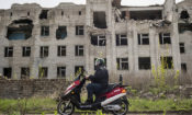 A cyclist rides his motorbike near a destroyed hospital in Slovyansk, Donetsk region, eastern Ukraine on Friday, April 19, 2019. (photo: AP/Evgeniy Maloletka)