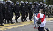 A woman covered herself by an old Belarusian national flag kneels in front of a riot police line as they block Belarusian opposition supporters rally in Minsk, Sept. 13, 2020. (photo: TUT.by via AP)
