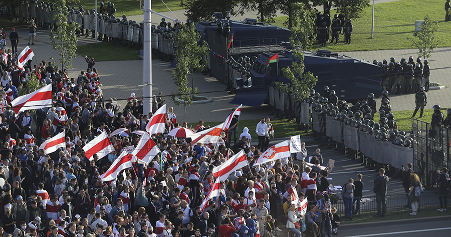 Protesters with old Belarusian national flags gather in front of a riot police line during a Belarusian opposition supporters' rally in Minsk, Sept. 13, 2020. (photo: TUT.by via AP)