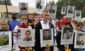 Relatives hold portraits of soldiers killed in a war conflict with Kremlin-backed separatists in eastern Ukraine, in front of the Russian Embassy in Kyiv, Ukraine, Friday, Aug. 28, 2020. (AP Photo/Efrem Lukatsky)