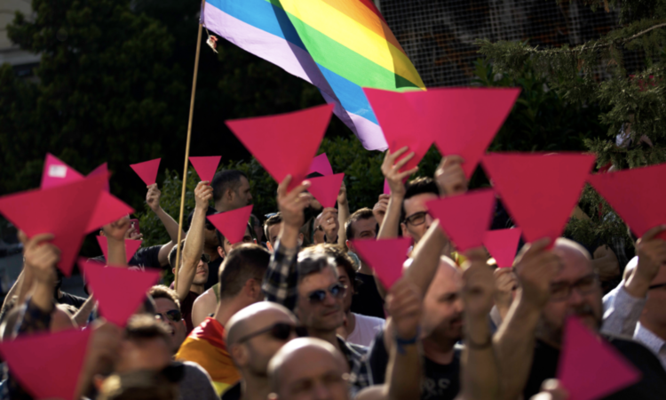 People hold up pink cardboard triangles and wave a rainbow flag during a gathering in support of the LGBT community in Chechnya. (Madrid, 2017. AP Photo)