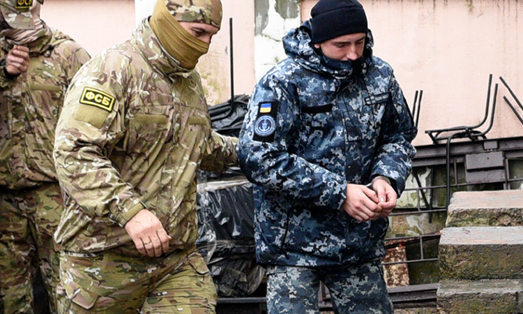 A Ukrainian sailor, right, is escorted by a Russian intelligence agency FSB .