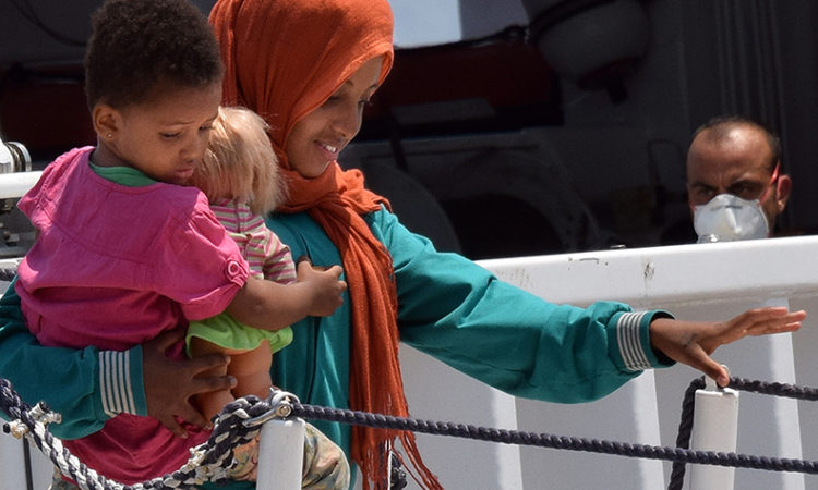A migrant carries a baby as she disembarks from a ship in Sicily, Italy, July 22, 2015. (AP Photo)