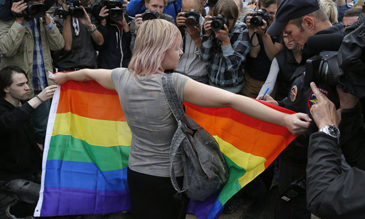 A gay rights activist stands with a rainbow flag, in front of journalists, during a protest in St.Petersburg, Russia, Sunday, Aug. 2, 2015. (AP Photo/Dmitry Lovetsky)