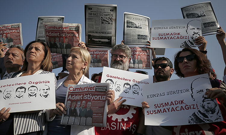 "Protesters hold copies of the Cumhuriyet newspaper with headlines in Turkish reading: ""We want justice"" and placards with pictures of arrested staff, as they protest against a trial of journalists and staff from the newspaper, Silivri, Turkey, Monday, Sept. 11, 2017. (AP photo)"