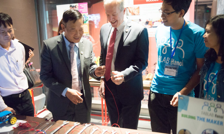 Ambassador Osius and Vice Minister of Science and Technology Tran Van Tung test out an electricity and music experiment by a participant in Hanoi.