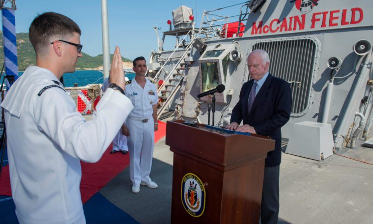 Senator John S. McCain III reenlists the ship's sailor of the year Electronics Technician 2nd Class Michael Papapietro during a visit to the Arleigh Burke-class guided-missile destroyer USS John S. McCain (DDG 56). The U.S. Navy has patrolled the Indo-Asia-Pacific routinely for more than 70 years promoting regional peace and security.
