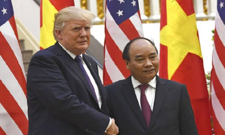 U.S. President Donald Trump, left, shakes hands with Vietnamese Prime Minister Nguyen Xuan Phuc in Hanoi Sunday, Nov. 12, 2017. (Hoang Dinh Nam/Pool Photo via AP)