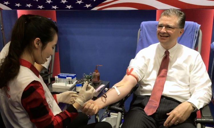 U.S. Ambassador Daniel Kritenbrink prepares to give blood.