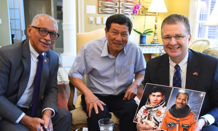 (From left) U.S. Science Envoy for Space, Major General Charles Frank Bolden, Jr. and Vietnamese cosmonaut, Lieutenant General Pham Tuan presenting their portraits serving as astronauts to their host, Ambassador Daniel Kritenbrink, at their meeting.