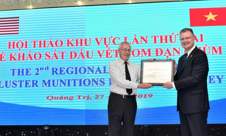 Ambassador Kritenbrink presents the certificate of appreciation from the U.S. Department of State to Mr. Phil Bean, UXO Program Advisor at the U.S. Embassy in Vientiane, who plays a key role in developing the Cluster Munitions Remnants Survey methodology.