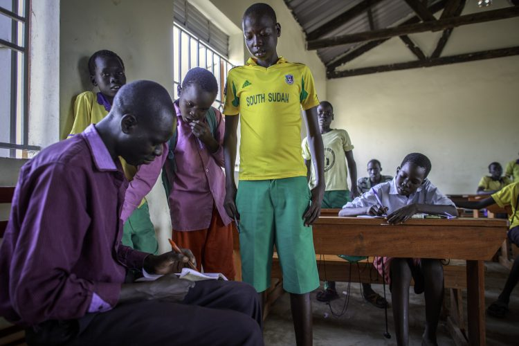 A teacher grade the work of students inside a newly constructed classroom at St. Luke's Primary School at Nyumanzi Refugee Settlemen in Northern Uganda 14 April 2015. UNHCR/J. Ose
