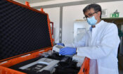 The IAEA's Giovanni Cattoli checks a package ready to be sent to assist in the fight against the COVID-19 virus. (Dean Calma/IAEA)