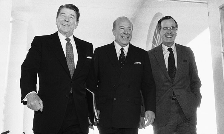 Secretary of State George Shultz, center, walks with President Reagan and Vice President George Bush on his arrival on Wednesday, Jan. 9, 1985 at the White House in Washington after two days of arms talks with the Soviet Union in Geneva. (AP Photo/Barry Thumma)