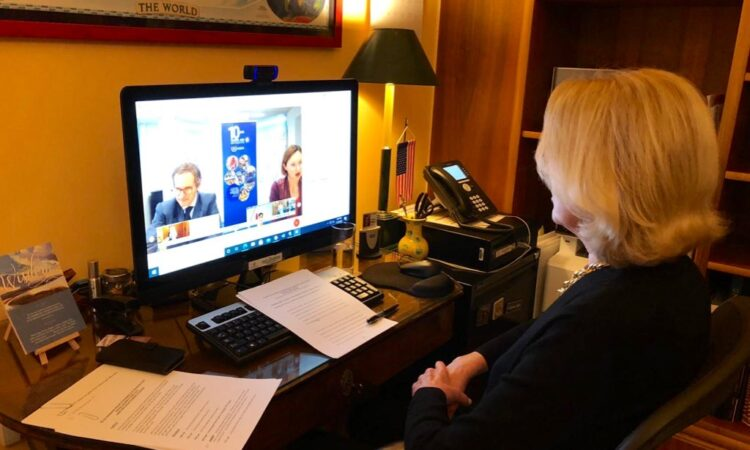 Female Ambassador sits at desk in home office looking at webinar on computer screen.
