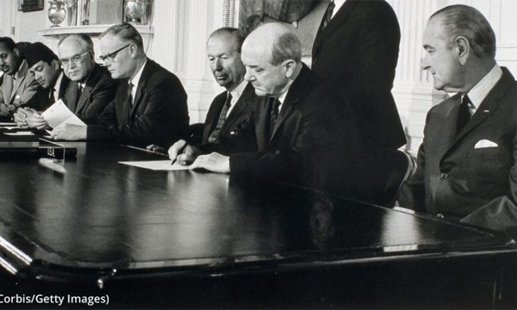 President Lyndon B. Johnson (far right) looks on as Secretary of State Dean Rusk signs the Nuclear Non-Proliferation Treaty in 1968. (© Corbis/Getty Images)