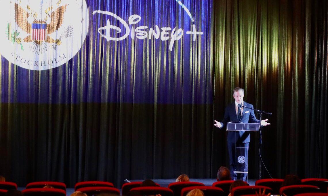 Man speaking in front of large backdrop reading Disney