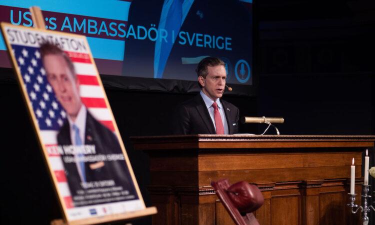 Ambassador standing behind a podium delivering remarks