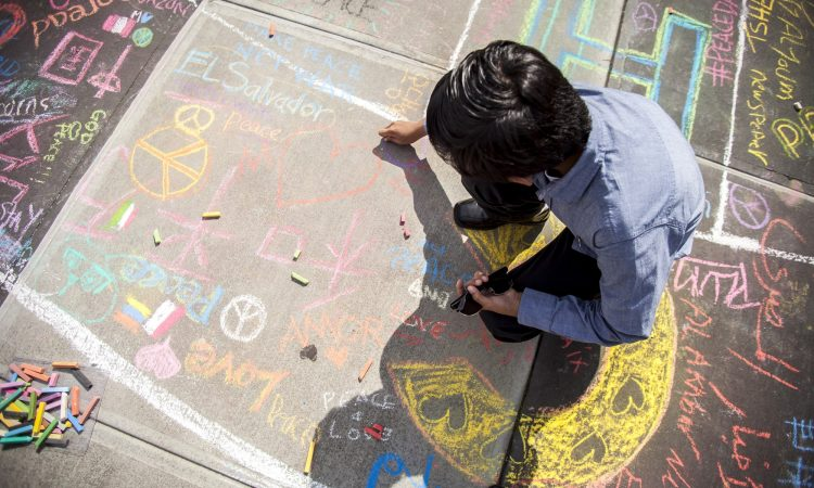 A young man leaves a message for peace, as a part of the global CHALK4PEACE art project, which was at UN headquarters during UNGA this week, for the observance of the International Day of Peace. [UN Photo]