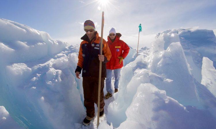 Un guide escorte le secrétaire d'État John Kerry à travers une zone où de gros blocs de glace se sont effondrés sur le sol près de la base Scott, dans l'Antarctique. (Département d'État)
