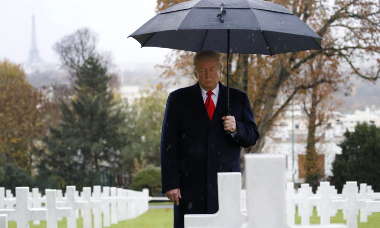 President Donald Trump stands amongst the headstones during an American Commemoration Ceremony, Sunday Nov. 11, 2018.