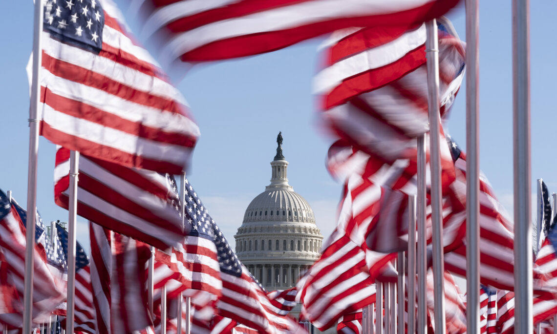 The U.S. Capitol is seen between flags