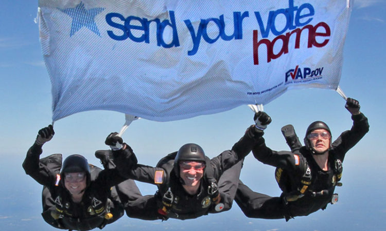 "Skydivers hold banner ""send your vote home"""