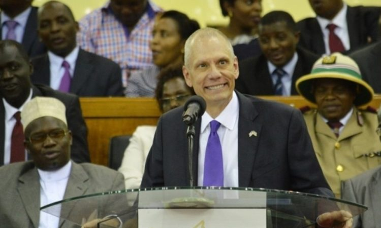 Ambassador Godec smiles at scholarship recipients from podium