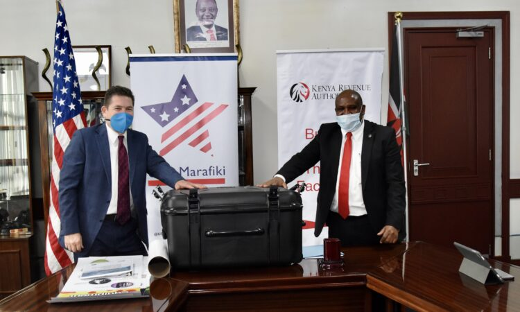 Photo 2 – U.S. Ambassador Kyle McCarter delivers a training kit for Kenya's front line customs and border control officials to KRA Commissioner General Githii Mburu.