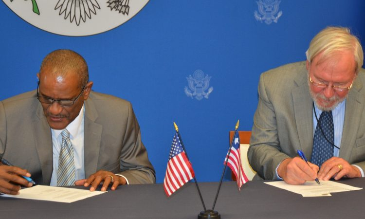 Two men sign an agreement.