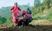 A female farmer operating a tilling machine.
