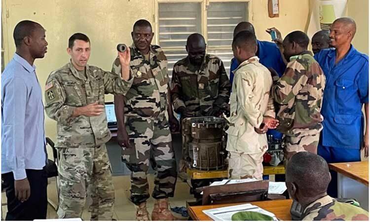 Des soldats américains et nigériens travaillent sur l'assemblage de la transmission Allison