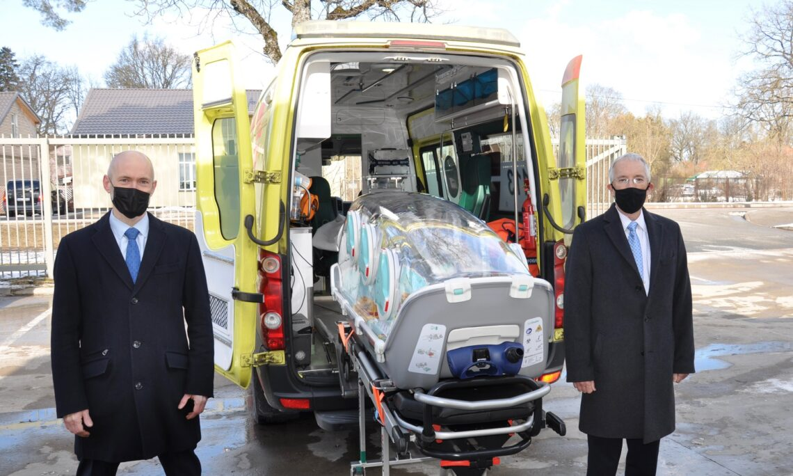 Two men standing next to the ambulance