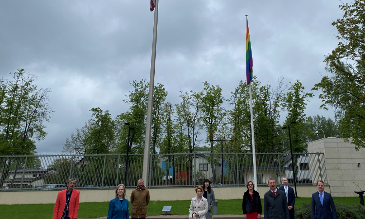 Several people standing by rainbow flag