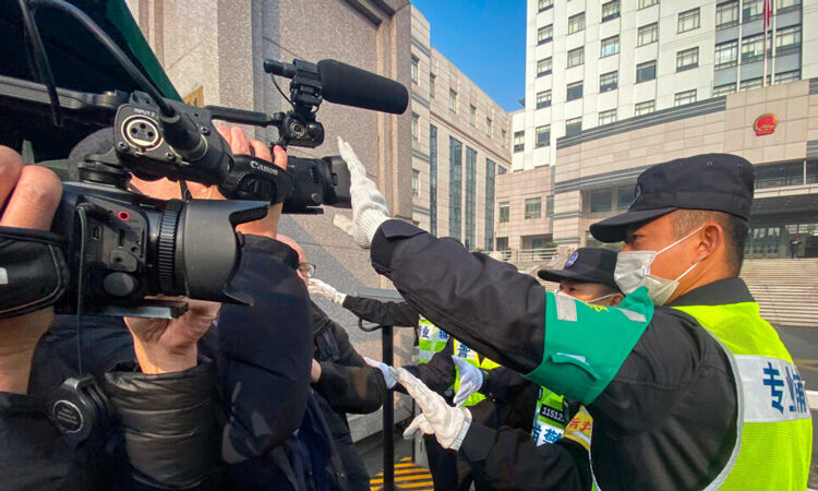 Police officers stop journalists from filming outside a Shanghai court where Zhang Zhan was on trial after reporting on the COVID-19 outbreak in Wuhan, China. (© Leo Ramirez/AFP/Getty Images)
