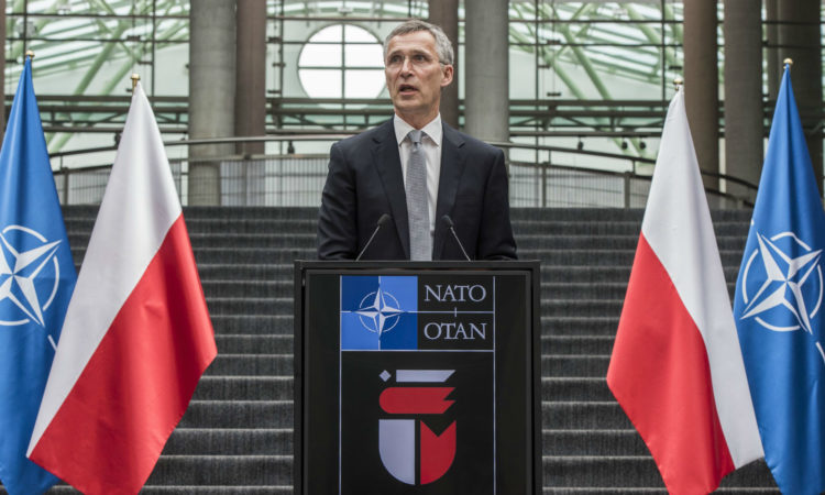 Secretary General Stoltenberg stands at podium in Waraw
