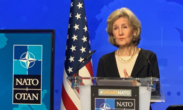 United States Ambassador to NATO Kay Bailey Hutchison behind the podium
