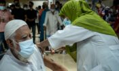 Man getting vaccine injection by woman. (Embassy Image)