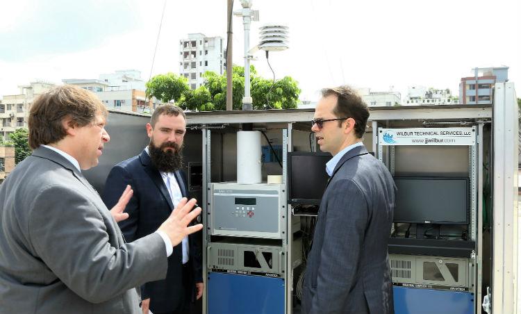 Three men talking outside. (Embassy Image)