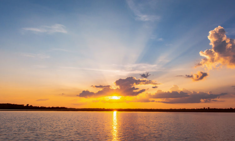 Sunset reflection lagoon. beautiful sunset behind the clouds and