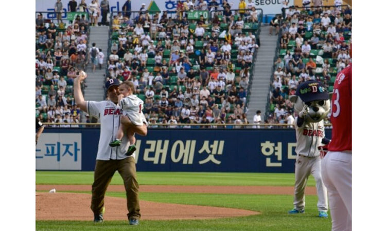 Ambassador Mark Lippert, holding his son Sejun, throws the first pitch at the '2016 Korea Baseball Organization League.'
