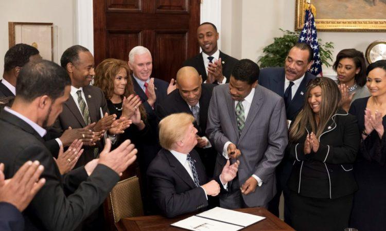 도널드 J. 트럼프 대통령이 마틴 루터 킹 기념일 선언문에 서명한 뒤 민권운동 지도자 마틴 루터 킹 주니어의 조카인 뉴턴 패리스 주니어에게 펜을 건네주고 있다.